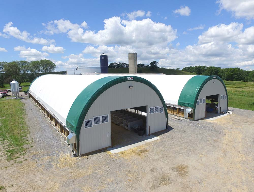 two large Better Fabric Structures set up on a farm