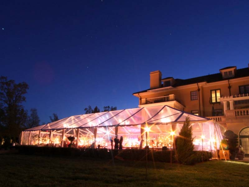 clear frame tent with sidewalls set up next to a building