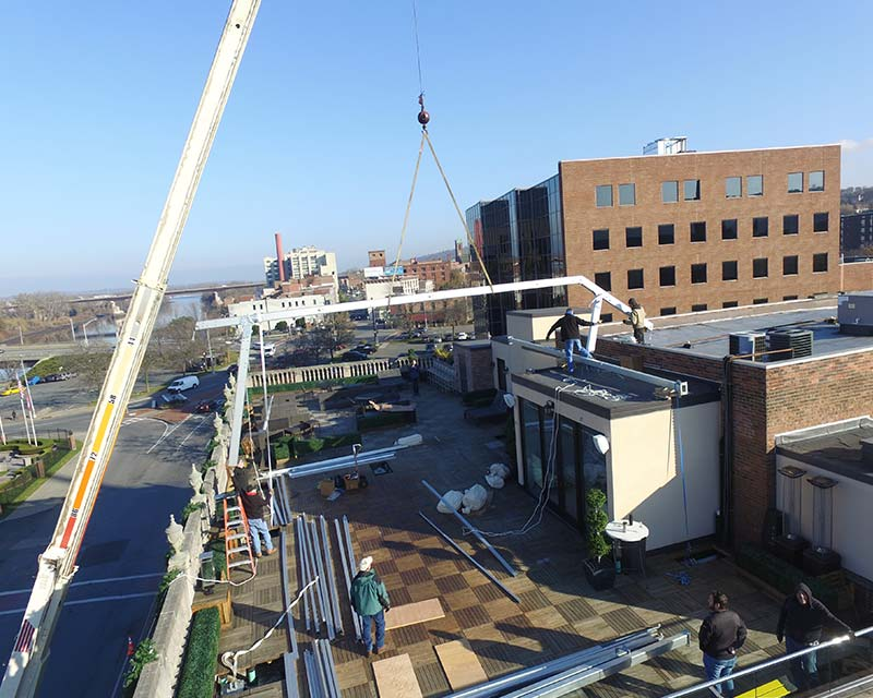 Crane setting up tent structure on top of roof