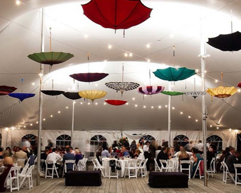 White wedding tent with umbrellas hanging from roof