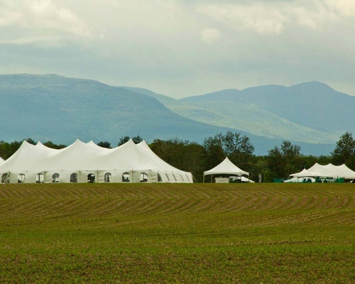 Large white tent setup near other smaller tents