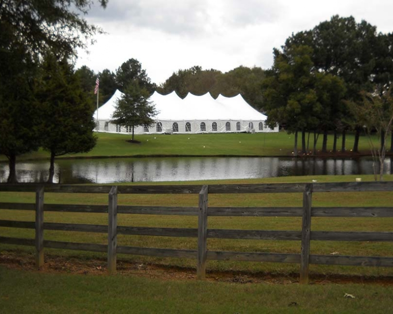 large wedding tent setup near pond