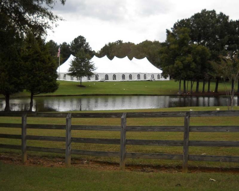 large wedding tent setup near pond