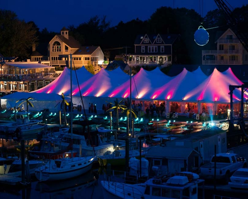 Tent setup in a marina with purple and red lights