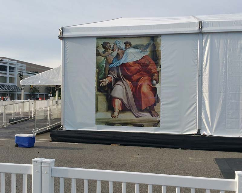 Large white tent in parking lot with custom graphics
