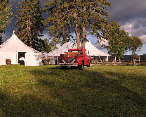 Old red pickup truck in from of white wedding tents