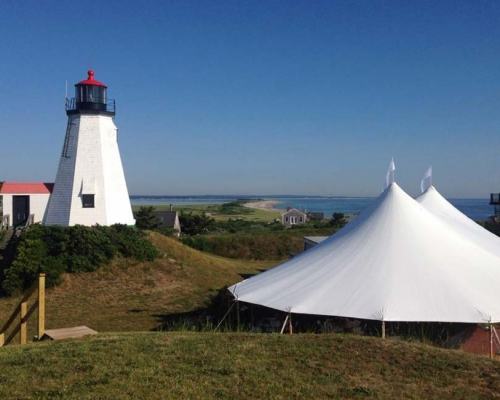Large wedding tent setup next to lighthouse