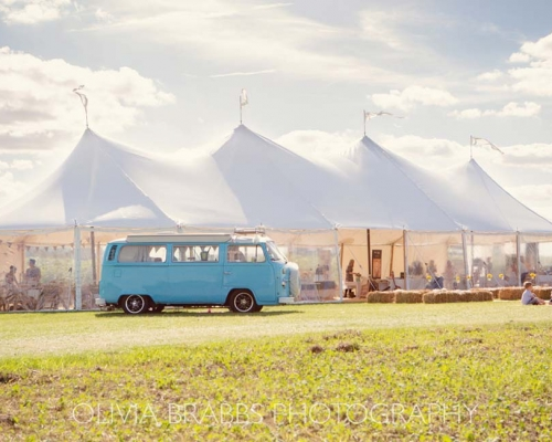 Old VW bus parked in from of large white tent