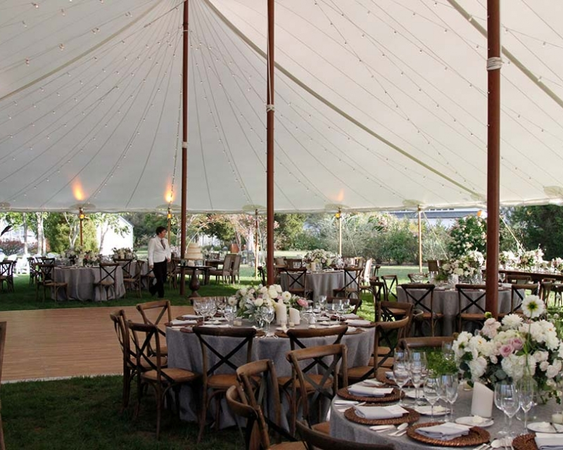 Tables and dance floor under large white tent