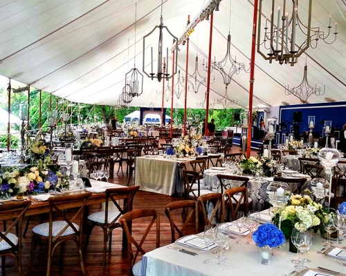 tables placing and chandeliers hung in tent