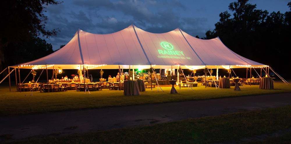 Sailcloth pole tent set up for a nighttime event.