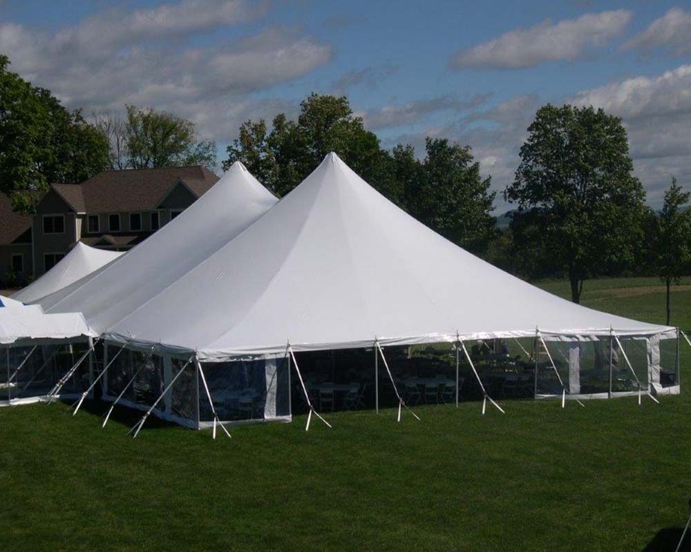Sailcloth pole tent with sidewalls setup in field