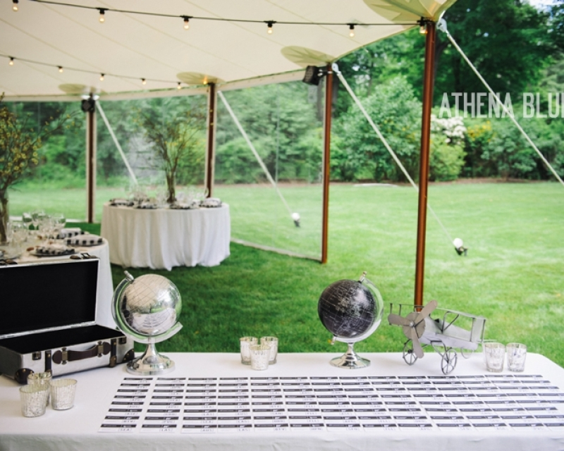 Table set up for wedding in a tent set up with wood finish side poles